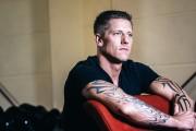 Bodybuilder lehnt lässig auf Handelbank