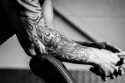 tätowierter Arm eines Mann geht auf einer Handelsbank im Fitnessstudio