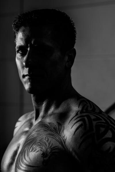schwarzweiß Portrait tätowiertem Bodybuilder mit freiem Oberkörper. Licht kommt von der Seite. Eine Gesichtshälfte dunkel