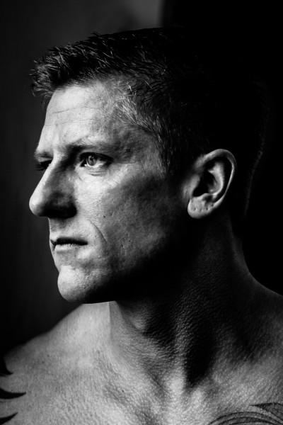 schwarzweiß Portrait mit freiem Oberkörper. Mann schaut aus Fenster