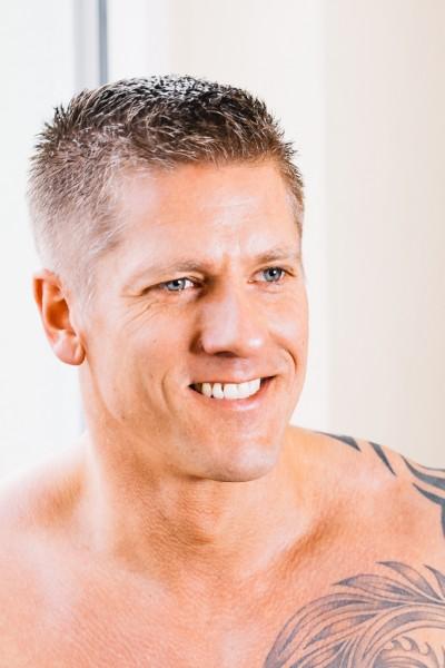 Bodybuilder mit freiem Oberkörper. Blick an Kamera vorbei