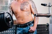 Bodybuilder mit freiem Oberkörper und Jeans steht lässig am Fenster im Fitnessstudio. Handeln im Vordergrund