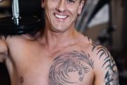 Bodybuilder mit freiem Oberkörper lächelt in Kamera. Auf der Schulter ist eine Handel aufgelegt.