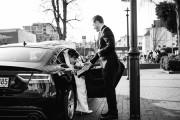 Fahrer hilft der Braut vor dem Standesamt in Oldenburg aus dem Auto auszusteigen