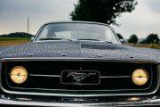 Frontale Ansicht vom 67er Ford Mustang mit Hengst und eingeschalteten Scheinwerfern