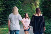 Familie läuft auf Strasse. Mädchen lächelt in die Kamera