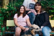 Familie sitzt mit Hund auf einer Bank im Wald