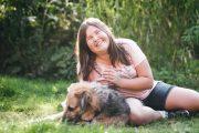 lachendes Mädchen liegt mit Hund auf einer Wiese. Streiflicht der Sonne auf ihrem Haar.