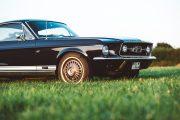 67er Ford Mustang von seitlich vorne. Perspektive von schräg unten. Wiese ist verschwommen im Vordergrund.