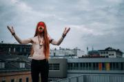 Model mit roten langen Haaren und freiem Oberkörper steht auf der Mauer und schreit mit offenen Händen