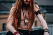 Model mit roten langen Haaren und freiem Oberkörper hockt auf der Mauer