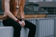 Model mit roten langen Haaren und freiem Oberkörper sitzt auf der Mauer, nachdenklicher Blick