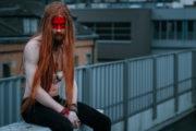 Model mit roten langen Haaren und freiem Oberkörper sitzt auf der Mauer, böser Blick