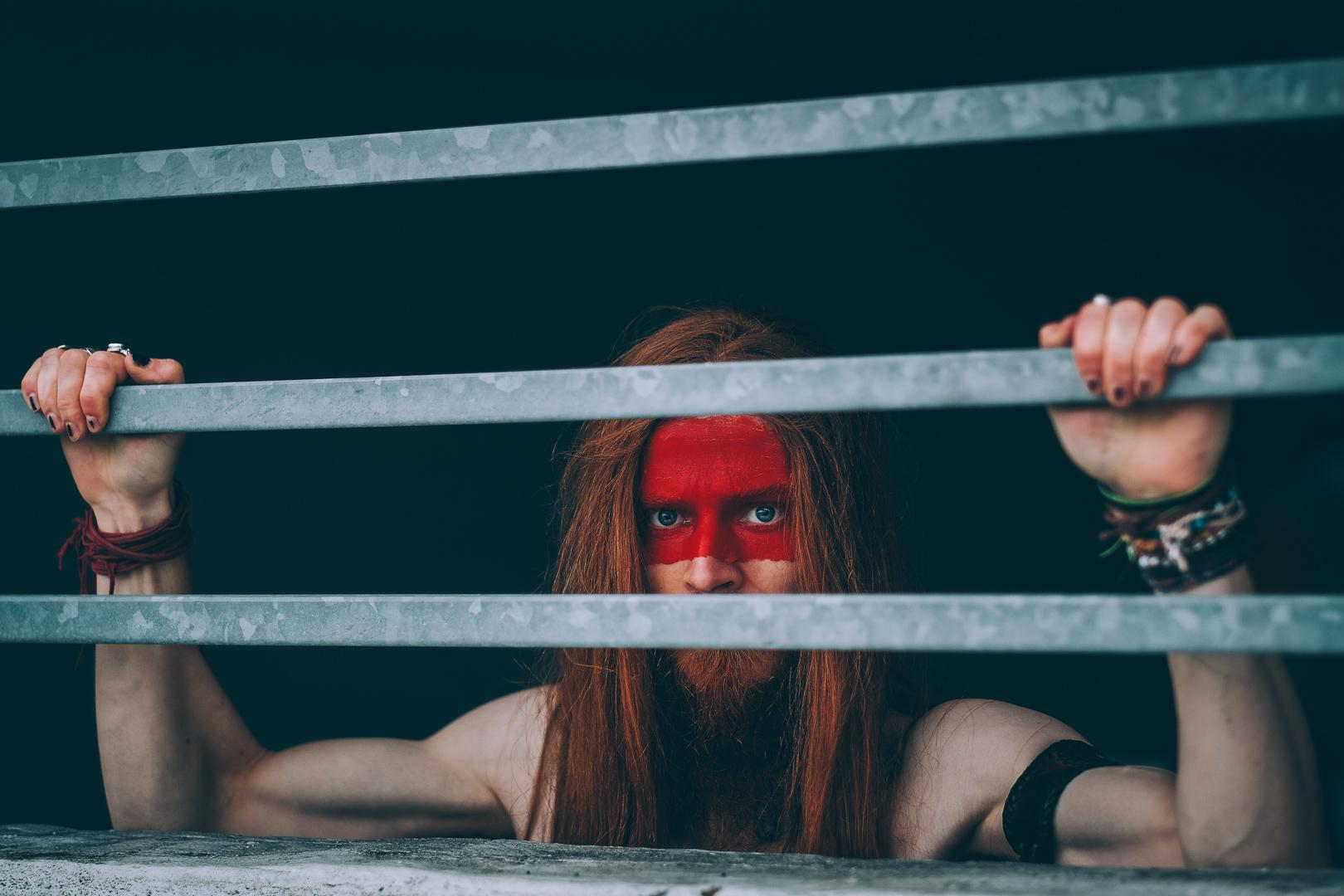 Model mit nacktem Oberkörper schaut hinter Gitter hervor. Er hält sich an den Stangen fest.