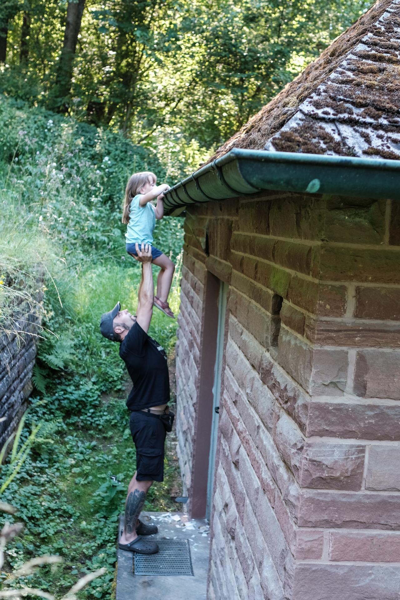 Mann hält Mädchen hoch um einen Geocache aus einer Dachrinne zu holen