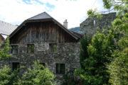 Altes Haus aus Bruchstein an Burgmauer