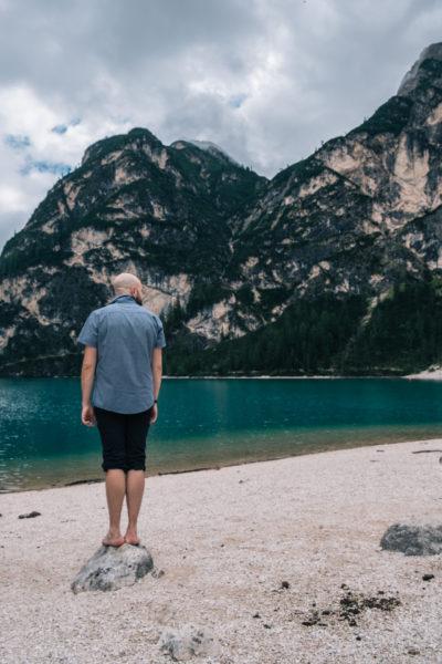 Pragser Wildsee, Mann steht am Strand auf Stein