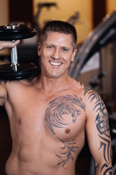 Portrait eines tätowierten und freundlichen Bodybuilder mit Hantel auf der Schulter