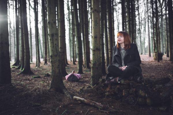 Portrait einer Frau. Olga sitzt auf einem Holzstapel im Wald. Sonnenlicht scheint durch die Bäume. Ein Korb steht im Hintergrund. Wirkt wie Rotkäppchen Märchen