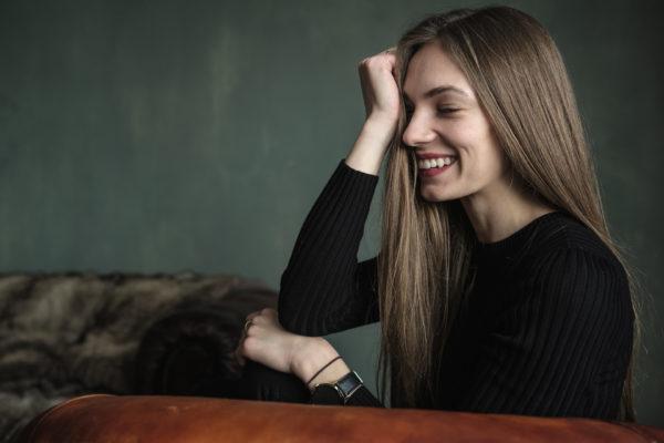 Portrait einer lachenden Frau welche seitlich auf einem Leder Sofa sitzt. Gemütliche und freundliche Stimmung
