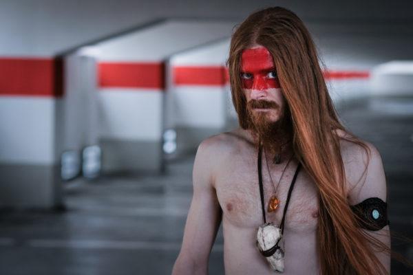 Portrait von einem Mann mit langen roten Harren. Das Gesicht ist zur hätte rot angemalt. Tribal Optik. Mann steht mit freiem Oberkörper im Parkhaus.