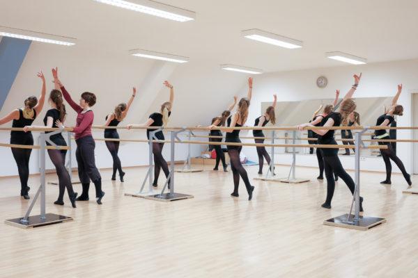Reportage bei Dance4Young. Coach Astrid Kronsbein zeigt einer Gruppe Übungen an der Balletstange