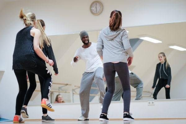 Reportage bei Dance4Young. Coach zeigt einer kleinen Gruppe HipHop Choreografie