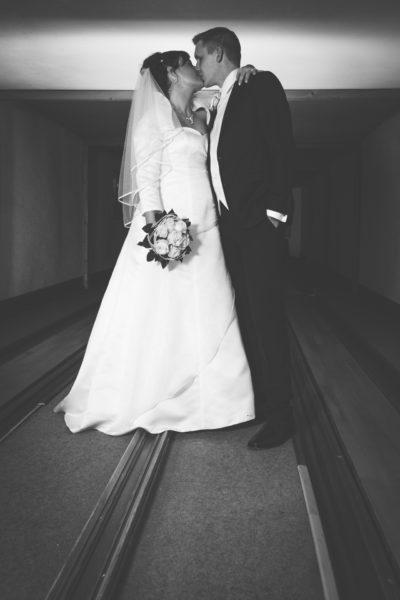 Reportage einer Hochzeit. Brautpaar steht auf einer Kegelbahn und küssen sich. Hochzeitsfoto in schwarzweiß.