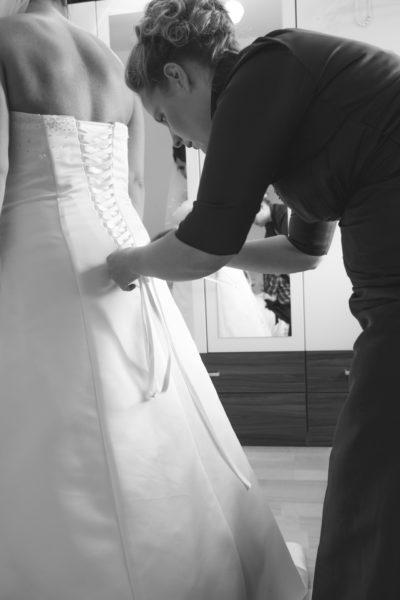 Reportage Hochzeit bei Ankleide. Trauzeugin hilft beim Anziehen des Brautkleid