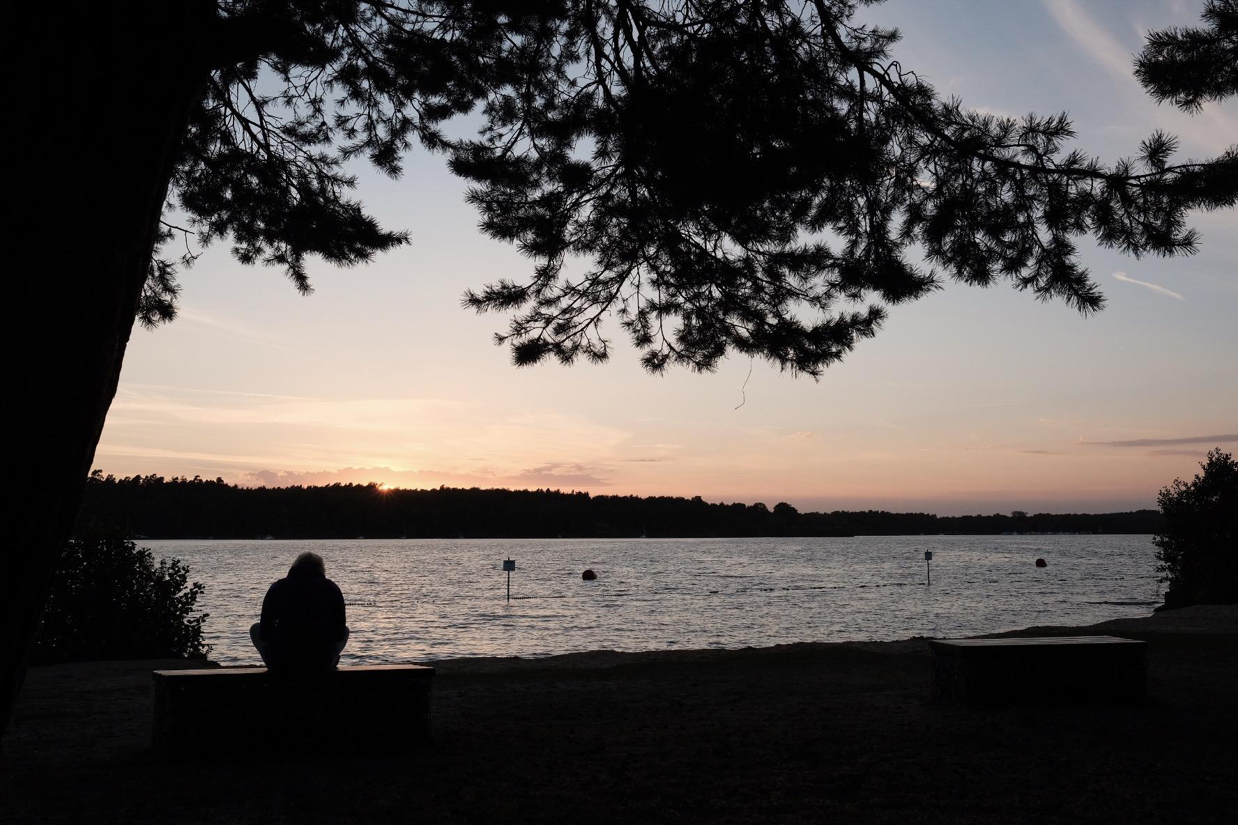 Frau sitzt am See beim Sonnenuntergang